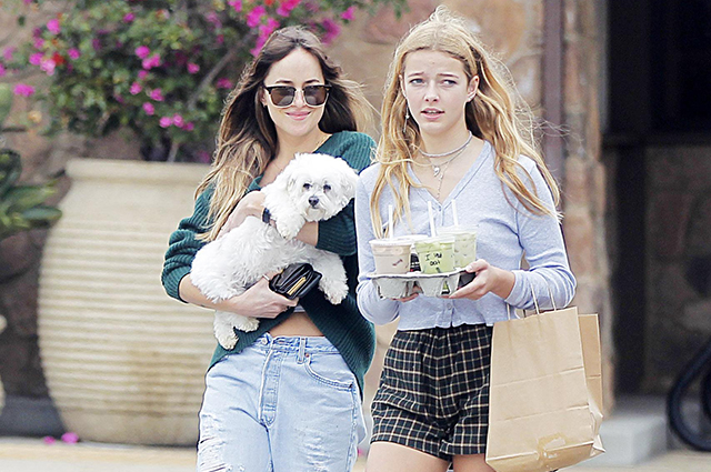 Like girlfriends: Dakota Johnson walks with her boyfriend Chris Martin's daughter